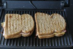 Сандвичи ветчины и сыра выпечки в кухне стоковые фотографии rf