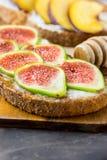 Сандвичи здравиц с плавленым сыром хлеба отрубей рож wholemeal, или югуртом, зрелыми смоквами и персиками Деревянный ковш меда Стоковое фото RF