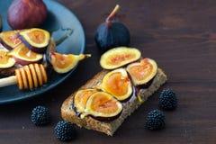Сандвичи с свежими смоквами, ягодами ежевики и медом на темной деревянной доске стоковая фотография rf