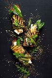 Сандвичи хлеба Wholemeal с сыром фета, зажаренным цукини, зеленой спаржей, горохами сахара, оливковым маслом на черной предпосылк стоковое изображение