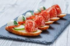 Сандвичи Caprese с томатом, сыром моццареллы, базиликом, салями на хлебе ciabatta на каменном конце предпосылки шифера вверх Стоковое Изображение