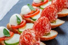 Сандвичи Caprese с томатом, сыром моццареллы, базиликом, салями на хлебе ciabatta на каменном конце предпосылки шифера вверх Стоковые Изображения