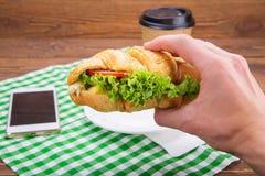 Сандвич круассана в руке Стоковые Изображения