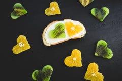 Сандвич с сливк и цитрусом с плодоовощ кивиа на черной таблице овощи шнура еды cauliflowers морковей фасолей естественные Плоское Стоковые Фотографии RF