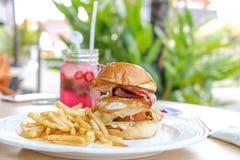 Сандвич с фраями бургера, томатов, сыра, салата и француза цыпленка Лимонад клубники на backgorund снаружи Стоковое Фото