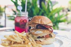 Сандвич с фраями бургера, томатов, сыра, салата и француза цыпленка Лимонад клубники на backgorund снаружи Стоковые Фотографии RF