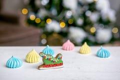 Сани и меренга пряника на таблице перед defocused светами ели украшенной рождеством Помадки праздника Новый Yea стоковое фото