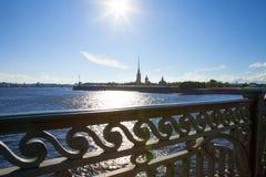 , Санкт-Петербург, мост Troitsky, взгляд Neva и Питер и крепость Пола, лучи через железную загородку Стоковое Фото