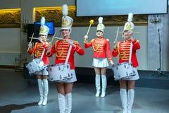 Санкт-Петербург, Россия - 15-ое декабря 2017: Девушки в красных формах с танцем барабанчиков Стоковые Изображения