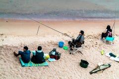 Санкт-Петербург, Россия - 10-ое июля 2018: Группа в составе рыболовы удит на песочных берегах Gulf of Finland под мостом стоковое изображение
