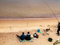 Санкт-Петербург, Россия - 10-ое июля 2018: Группа в составе рыболовы удит на песочных берегах Gulf of Finland под мостом стоковые изображения