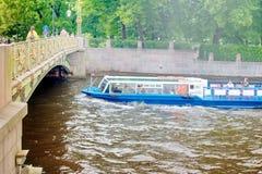 Санкт-Петербург, Россия - 7-ое июля 2017: Прогулочные катера носят туристов на реках и каналах Идет под мост стоковое изображение rf