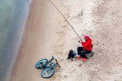Санкт-Петербург, Россия - 10-ое июля 2018: рыболов удит на песочных берегах Gulf of Finland под мостом стоковые фотографии rf