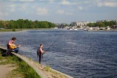 Санкт-Петербург, Россия - 21-ое мая 2014: gitarist и fishermansitting - стоящ на реке niva, солнечном дне стоковое фото