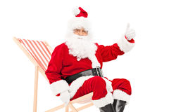 Санта давая большой палец руки вверх усаженный в lounger солнца Стоковые Изображения
