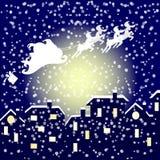 Санта в его санях летая над городом Стоковые Изображения