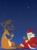 Санта и северный олень играя smartphone Стоковое Изображение