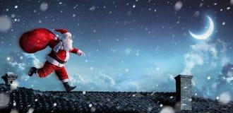Санта Клаус бежать на крышах стоковое изображение