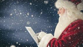 Санта Клаус взаимодействуя с его планшетом совмещенным с падая снегом сток-видео