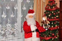 Санта Клаус давая подарки дереву на времени рождества стоковое фото