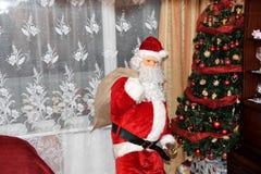 Санта Клаус давая подарки дереву на времени рождества стоковые изображения