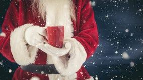 Санта Клаус держа горячий напиток совмещенный с падая снегом сток-видео