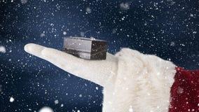 Санта Клаус держа настоящий момент в его руке совмещенной с падая снегом акции видеоматериалы