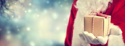 Санта Клаус держа подарок Стоковое Изображение