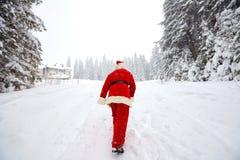 Санта Клаус идет в древесины в зиме на рождестве Стоковое Фото