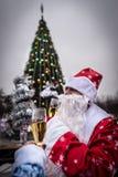 Санта Клаус и девушка снега празднуют Новый Год около рождественской елки Стоковое фото RF