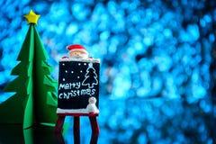 Санта Клаус и подарки и игрушки на lig стеклянного стола и сини bokeh Стоковое Изображение