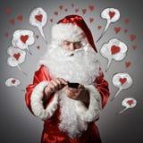 Санта Клаус и умный телефон человек влюбленности поцелуя принципиальной схемы к женщине стоковые фото