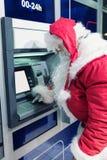 Санта Клаус на машине ATM Стоковое Фото