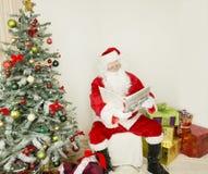 Санта Клаус на стуле в сцене праздника Стоковое фото RF