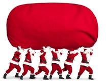 Санта Клаус нося мешок большого и тяжелого подарка красный стоковое изображение rf