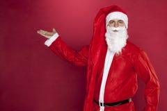 Санта Клаус показывает красный космос предпосылки и экземпляра на ем Стоковая Фотография
