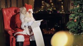 Санта Клаус сидит в его стуле перед рождественской елкой читая список подарка Нового Года сток-видео