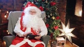 Санта Клаус смотря таблетку видеоматериал