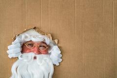 Санта Клаус смотря через отверстие на картоне Стоковое Изображение