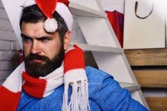 Санта Клаус стоит около белых лестницы и полок на белой предпосылке кирпича Праздники и концепция настоящих моментов парень с стоковое изображение rf