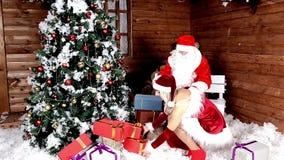 Санта Клаус с моей племянницей для подготовки сумки с подарками для слушая детей Атмосфера Xmas Новый Год рождества счастливое сток-видео