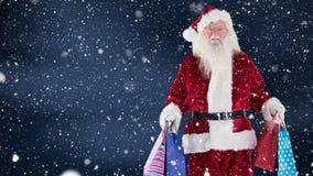 Санта Клаус с хозяйственными сумками совмещенными с падая снегом видеоматериал