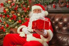 Санта Клаус с giftbox на предпосылке сверкнать ели Chr стоковые изображения