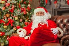 Санта Клаус с giftbox на предпосылке сверкнать ели Chr стоковые изображения rf