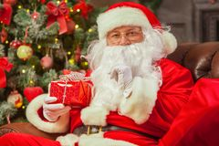 Санта Клаус с giftbox на предпосылке сверкнать ели Chr стоковое фото rf