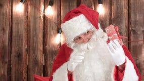 Санта Клаус тряся малый подарок tryring для того чтобы угадать какое ` s внутрь стоковые изображения
