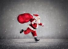 Санта Клаус бежать с сумкой a подарков на пути Стоковое фото RF