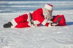 Санта Клаус лежа на снеге, смотря новости компьтер-книжки Стоковые Изображения RF