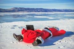 Санта Клаус лежа на снеге, смотря новости компьтер-книжки Стоковая Фотография