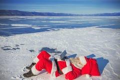 Санта Клаус лежа на снеге, смотря новости компьтер-книжки Стоковое Изображение